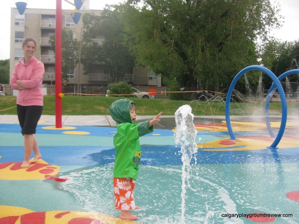 Kid playing in Calgary's rotary park spray park in the rain