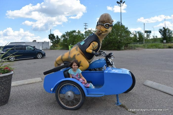 Dinosaur driving a motorcycle statue - Drumheller With Kids
