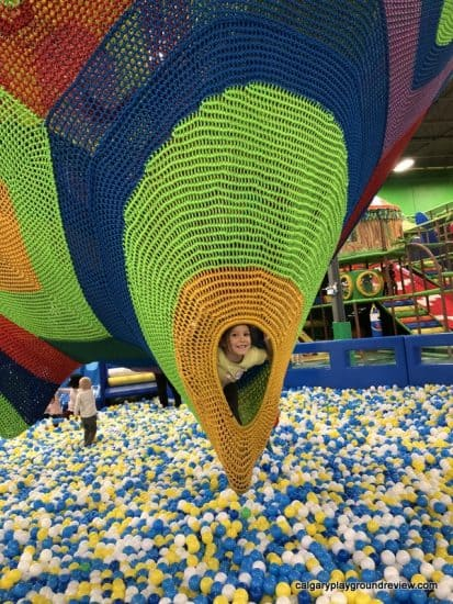 child peaking out of the net climber