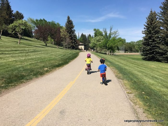 kids riding bikes towards the Confederation Park Natural Playground